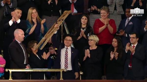 ▲트럼프 대통령의 소개로 자리에서 일어나 자신의 목발을 들어 보이고 있는 지성호 씨 ⓒ백악관 유튜브 영상 캡쳐